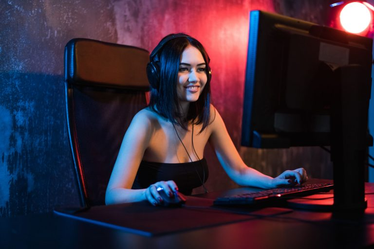 A cute female gamer girl sits in a cozy room behind a computer and plays games