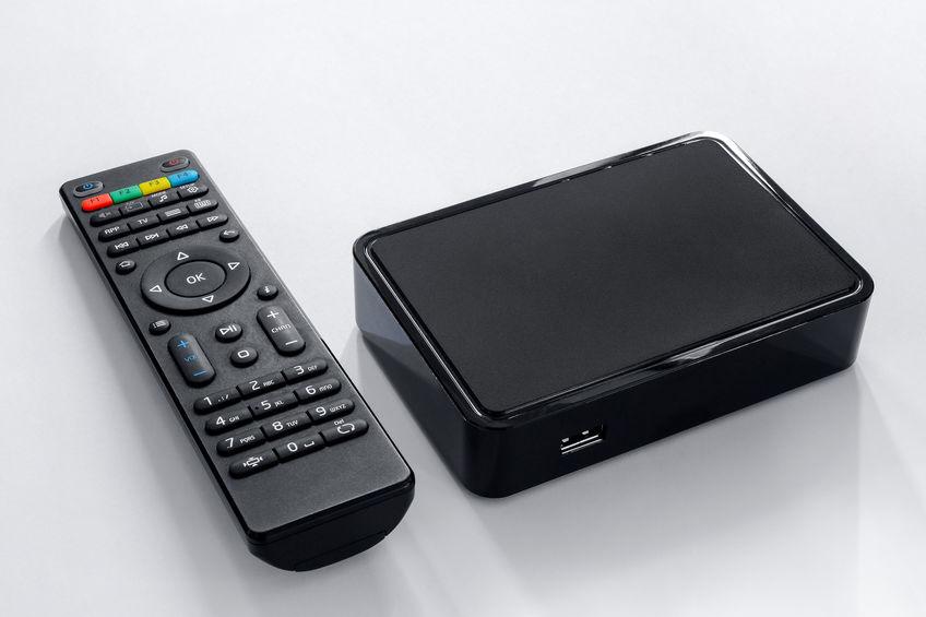 Iptv-box en afstandsbediening. Modern multimedia-apparaat voor televisiekijken via internet, multimediaspeler en bedieningspaneel.