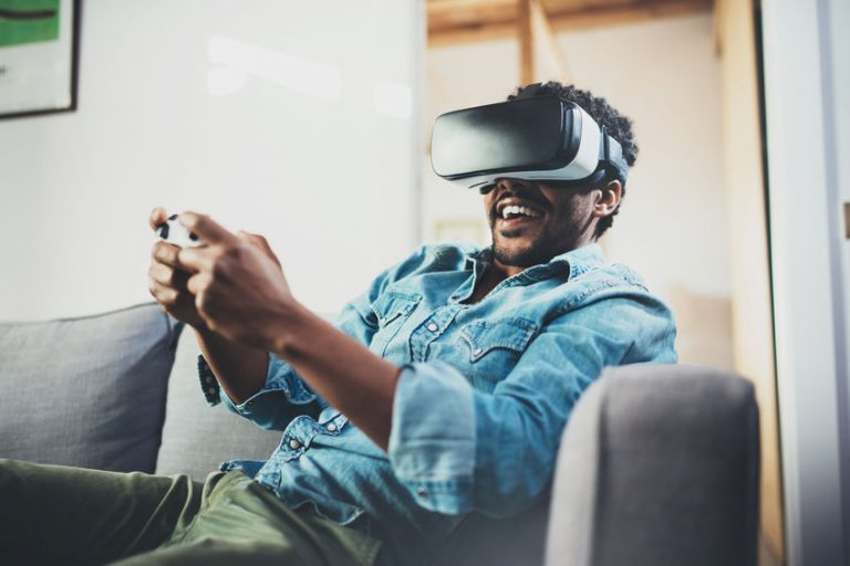 Smiling african man enjoying virtual reality glasses while sitting on sofa.Happy young guy with vr headset or 3d spectacles and controller gamepad