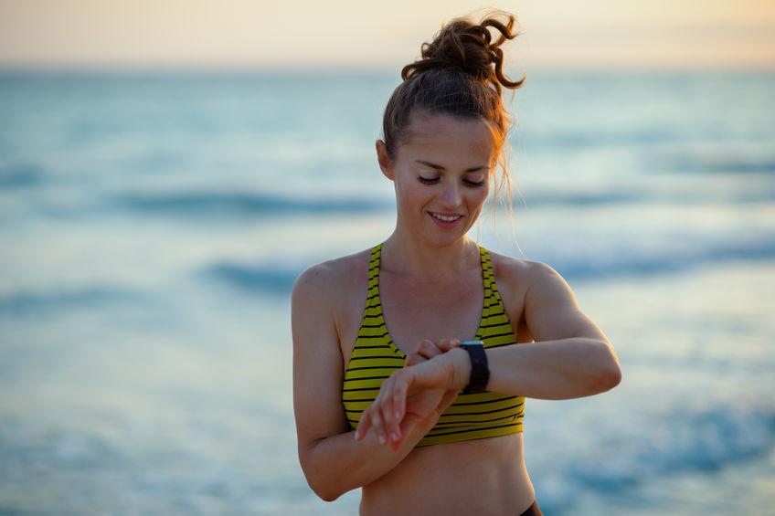 Girl watching her smartwatch in the beach