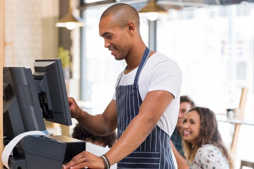 Young waiter doing bill