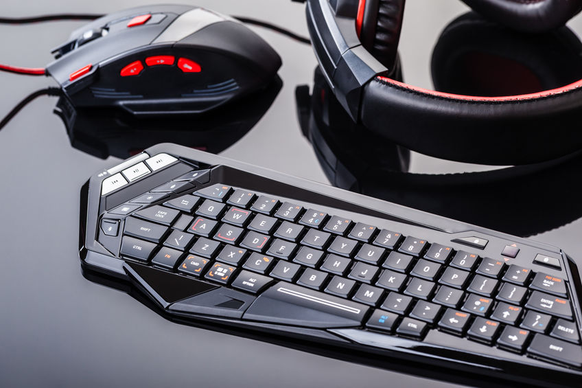 a gaming keyboard, mouse and headset shot over a dark reflective surface