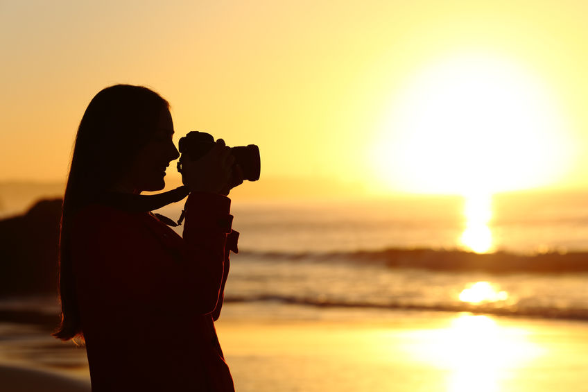 Side view of a photographer photographing the sun silhouette against the light with a DSLR camera