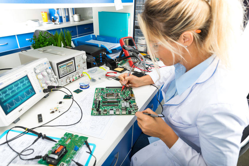 Female electronic engineer testing computer motherboard in labor