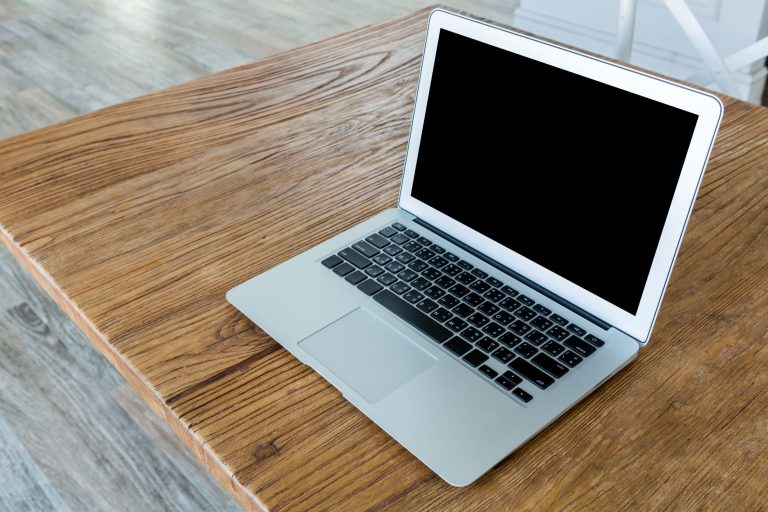 Blank screen laptop computer on wood table