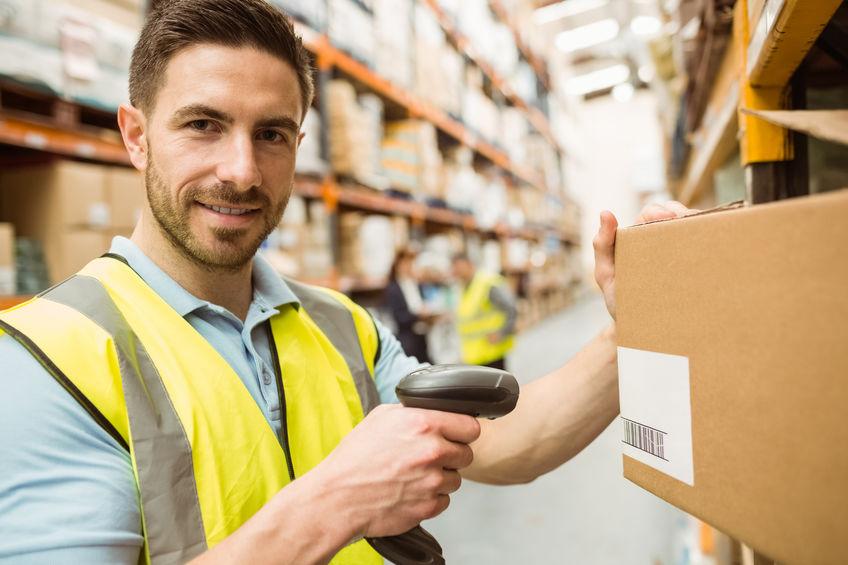 Magazijnmedewerker scannen doos terwijl lachend naar de camera in een groot magazijn