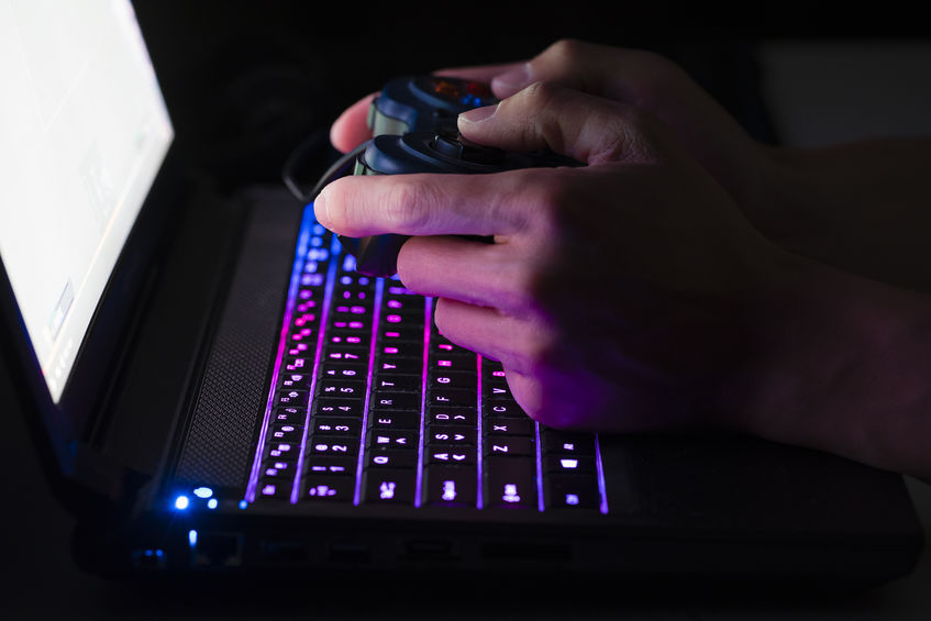 Playing computer game on laptop with joypad