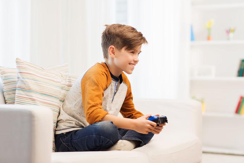gelukkige jongen met joystick spelen van videogame thuis