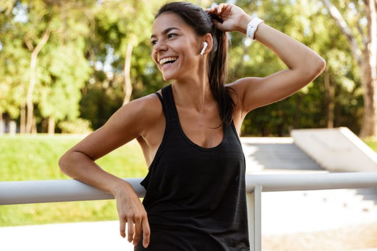 Portrait of a laughing fitness woman leaning on a rail