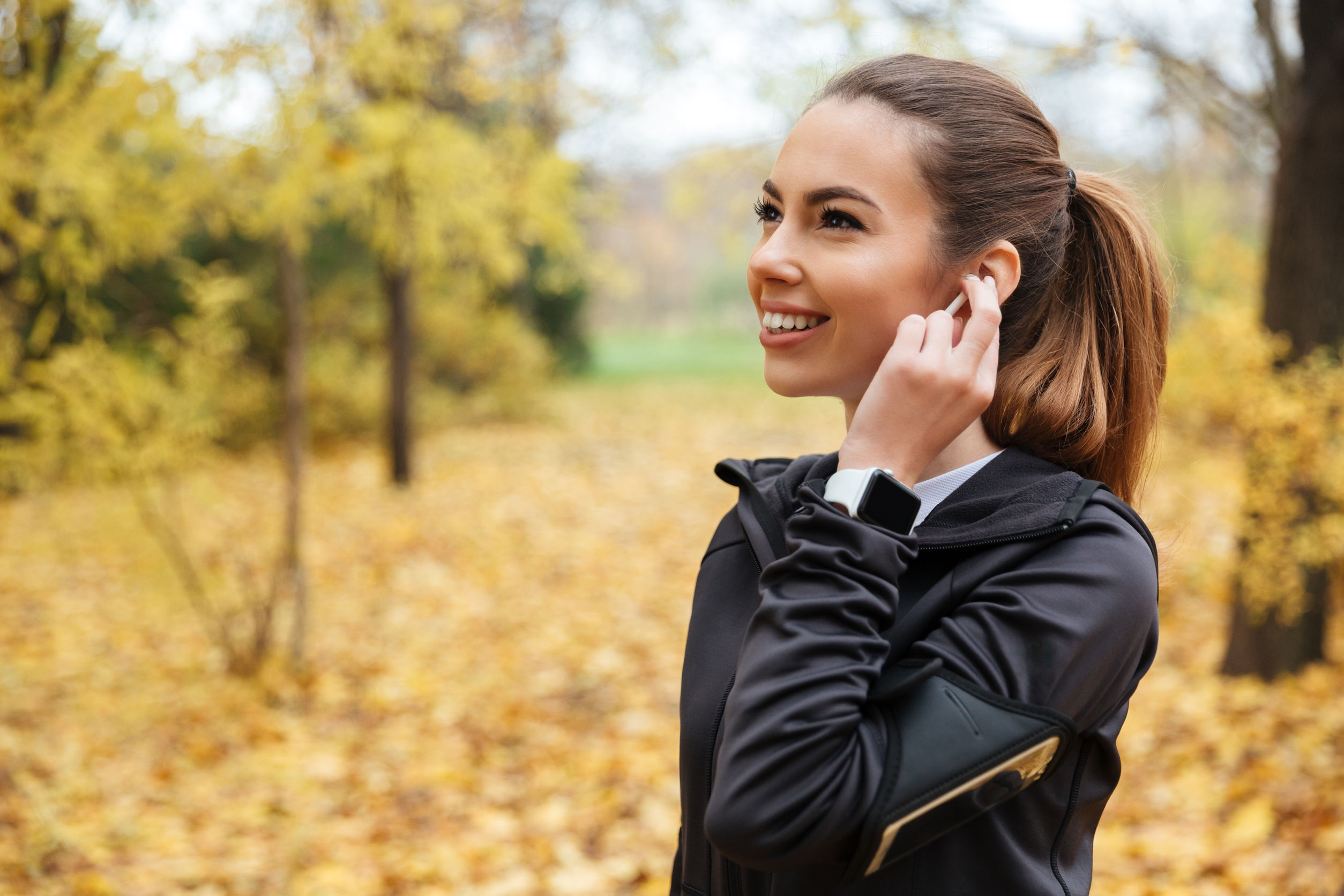 Portrait of a smiling fitness girl listening to music