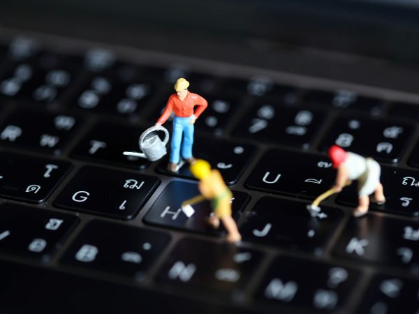 Miniature people worker team with button on a computer keyboard.