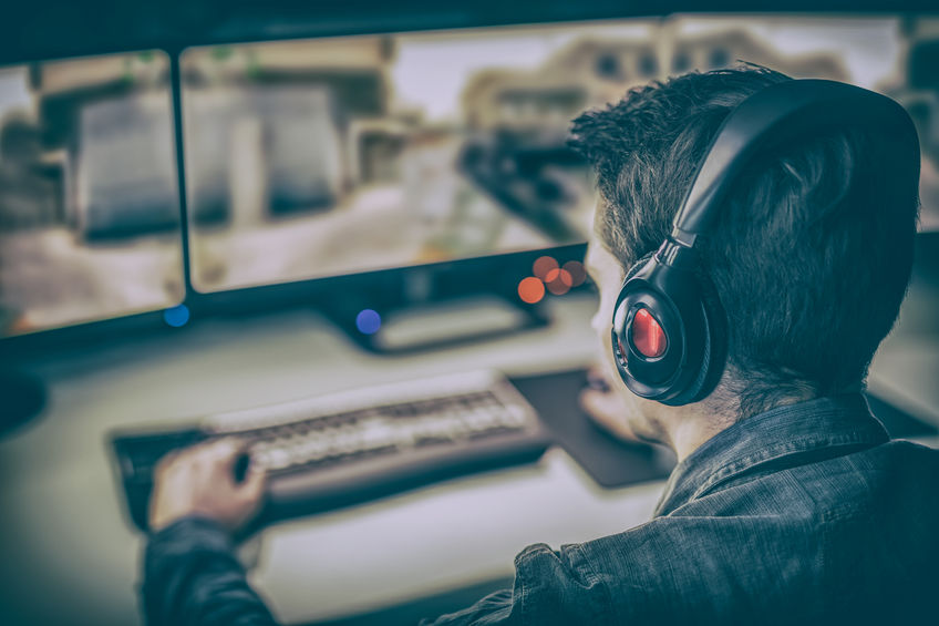 A professional computer player plays on a computer using two monitors.