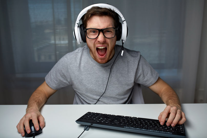technology, gaming, entertainment, let's play and people concept - angry screaming young man in headset with pc computer playing game at home and streaming playthrough or walkthrough video