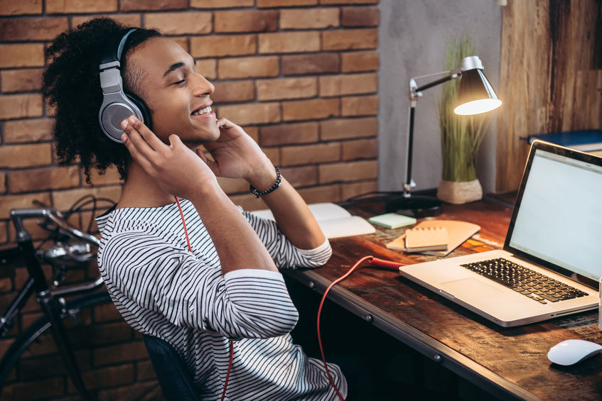 Side view of cheerful young African man adjusting headphones and keeping eyes closed while sitting at his working place