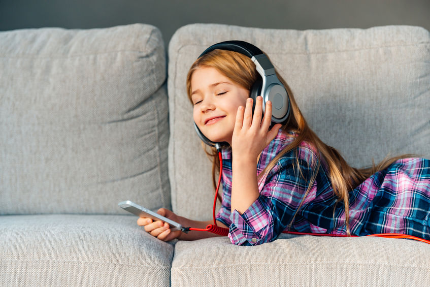 Enjoying music at home. Beautiful little girl adjusting her headphones with smile while lying on front on the couch at home