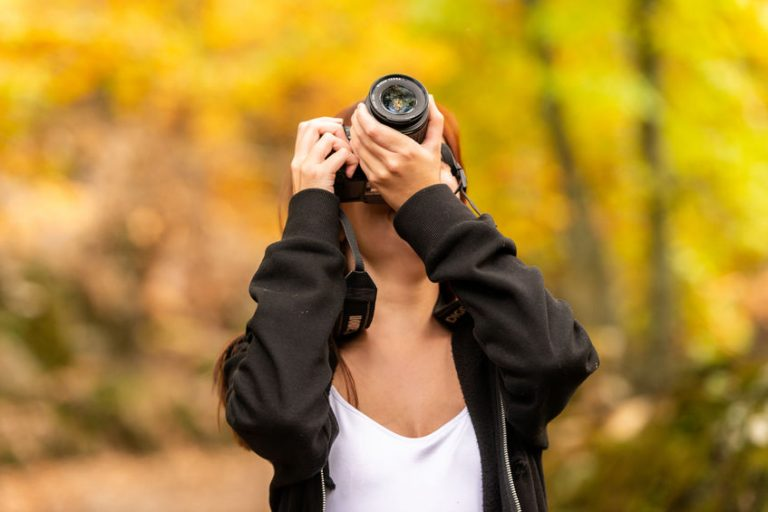 A young woman with reddish hair takes pictures with a reflex camera in a forest