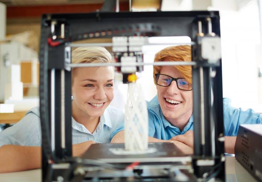 Dois engenheiros aguardando sorrindo por um projeto sendo impresso na impressora 3D.
