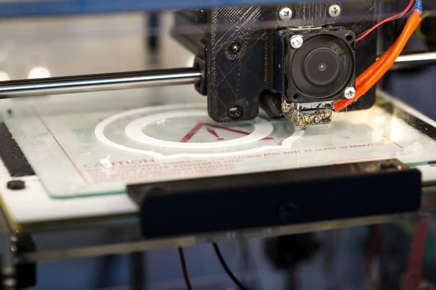 Imagem mostra uma impressora 3D em funcionamento.