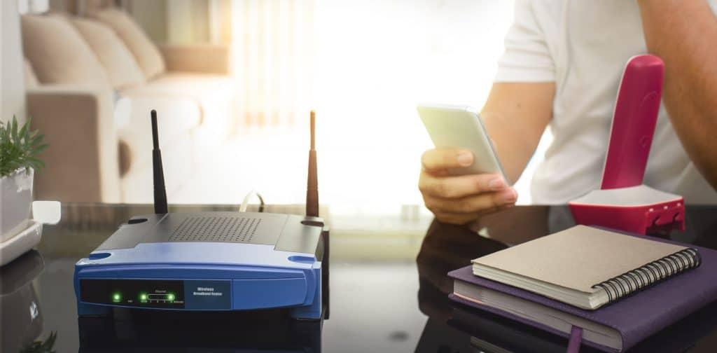 Imagem mostra um roteador com antenas wifi e um homem mexendo no celular ao fundo.
