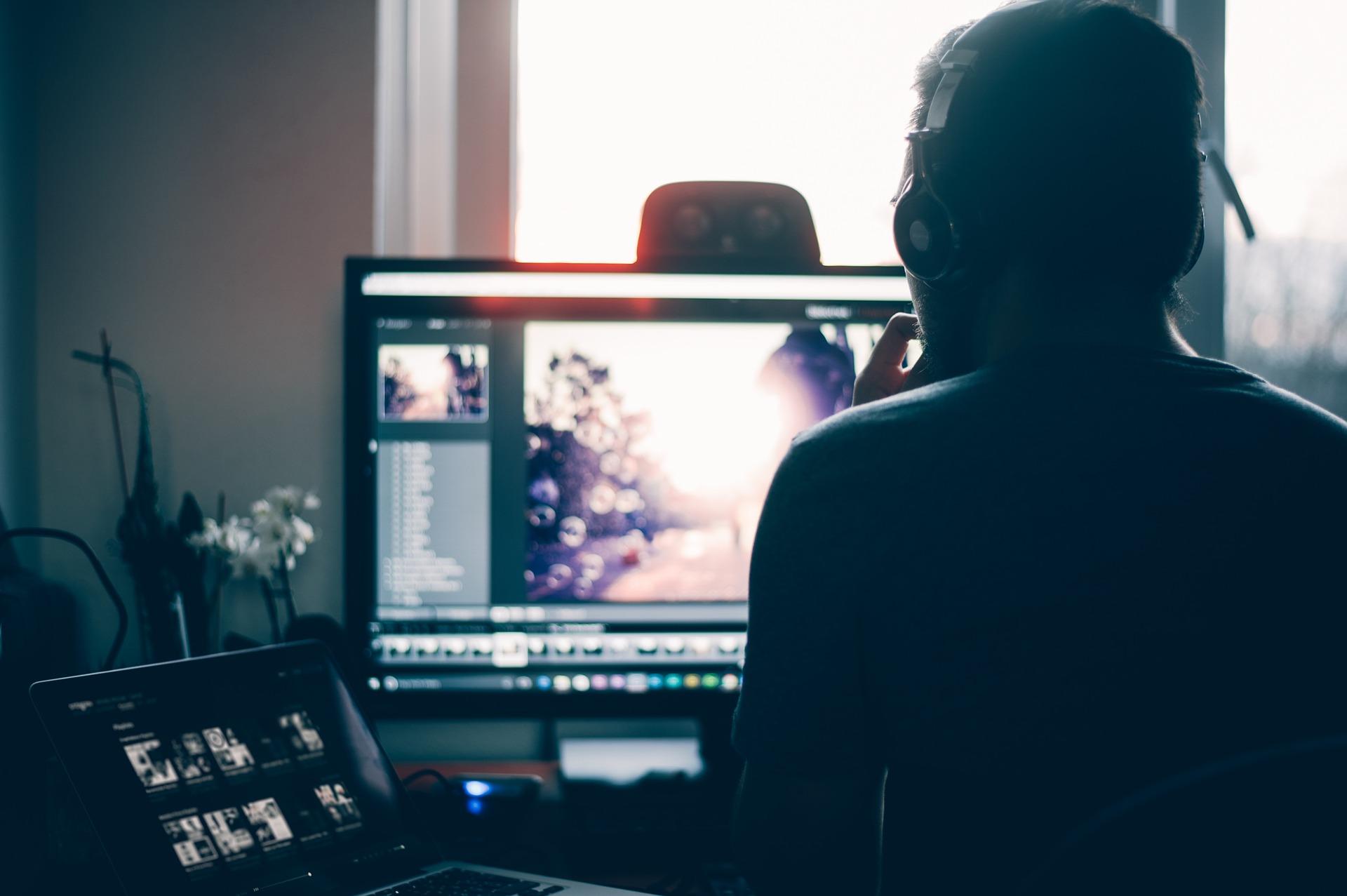 Imagem mostra um homem fazendo edição de imagem com um headset.
