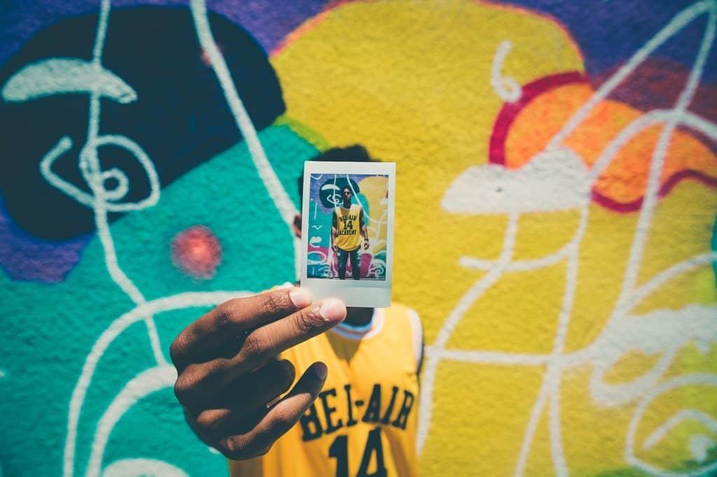 Rapaz exibe foto instantânea em frente a muro grafitado onde ela foi tirada.