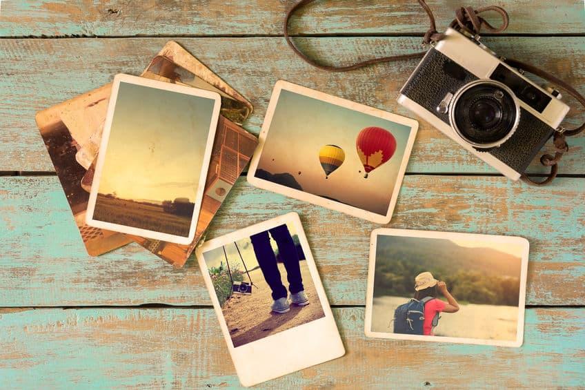 Imagem de fotografias sobre mesa com câmera ao lado.