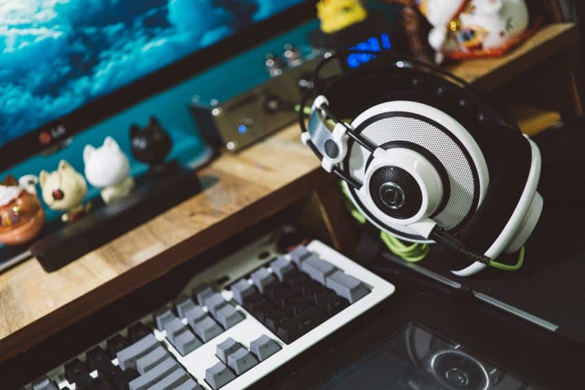 Imagem mostra um espaço gamer, com monitor de PC, teclado e headset gamer branco com detalhes em preto.