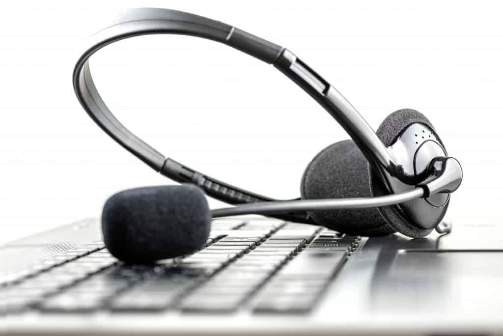 fone de ouvido com microfone posicionado sobre o teclado de um computador