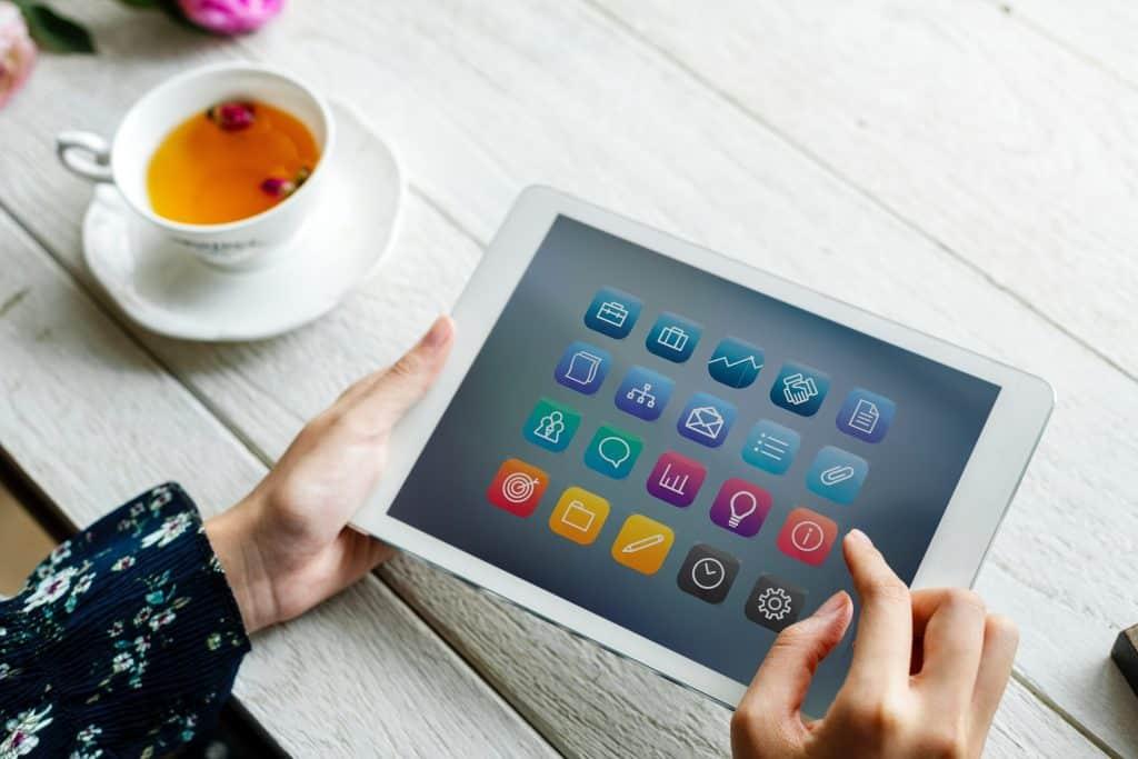 Imagem de pessoa mexendo em tablet com xícara de chá ao lado.