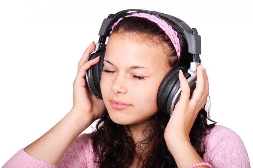 Imagem de uma menina utilizando um fone de ouvido sem fio.