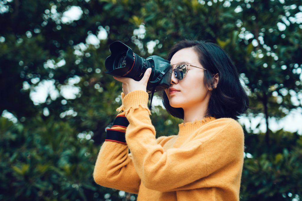 Imagem de uma jovem tirando foto.
