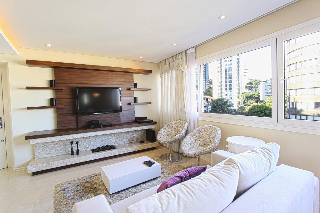 Na foto uma sala de estar com um sofá branco, poltronas estampadas e um painel de TV em madeira.