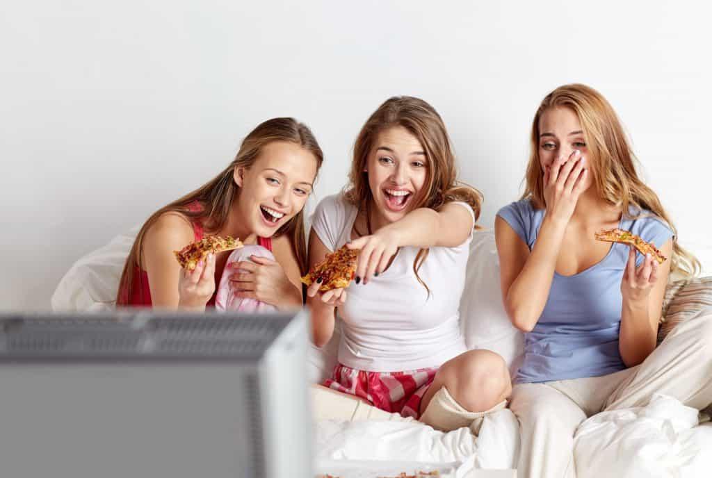 Imagem de três garotas assistindo televisão e comendo pizza.