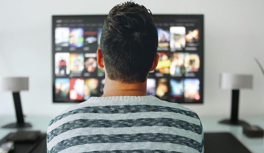 Na foto está um homem sentado de costas utilizando blusa listrada branca e verde olhando para um aparelho de TV ligado.