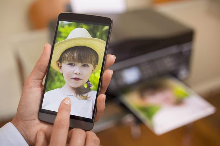 Mão de mulher segurando celular e imprimindo foto através dele.