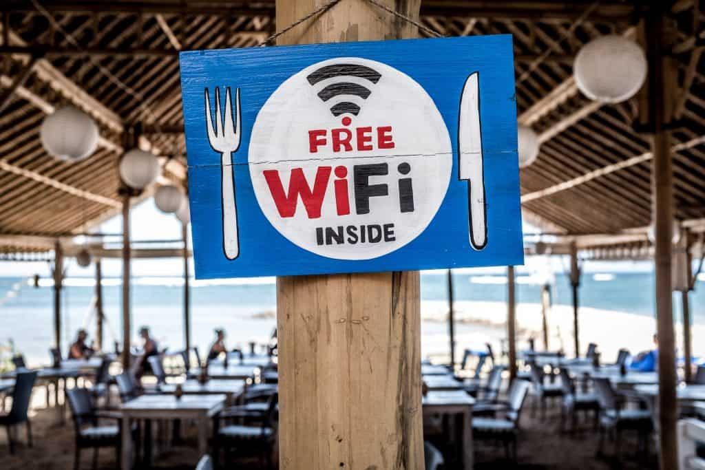Imagem mostra uma placa de wifi grátis com um grande restaurante ao fundo.